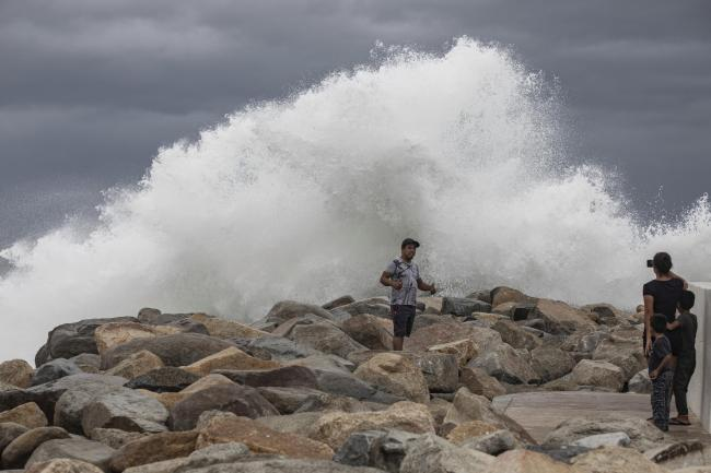 A tourist poses for a photo in front of breaking waves before the expected arrival of Hurricane Lorena, in Los Cabos, Mexico