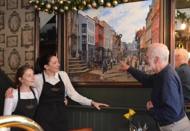 Artist Don Lavelle points out one of the characters in his latest painting to staff at Greens