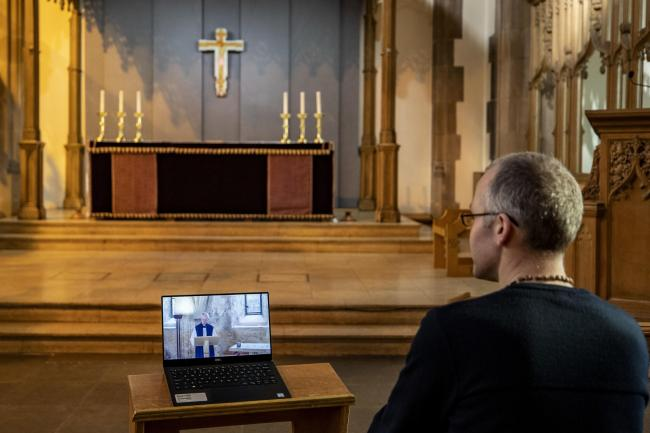 A parishioner watches a laptop inside Liverpool Parish Church (Our Lady and St Nicholas), during the Church of England's first virtual Sunday service