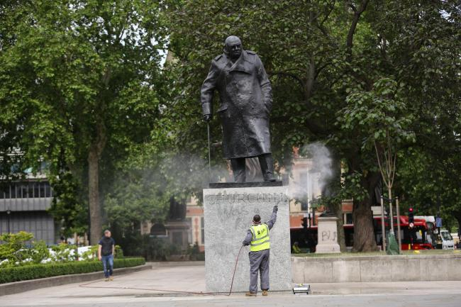 A worker cleans graffiti from the plinth of the statue of Sir Winston Churchill at Parliament Square in London, following a Black Lives Matter protest at the weekend. A raft of protests across the UK were sparked by the death of George Floyd, who was kill