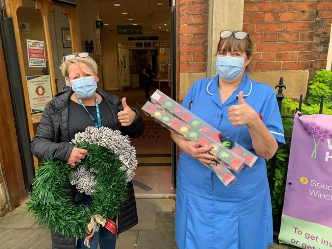 Lynn Eathorne-Long and Heather Farmiloe from The Royal Hampshire County Hospital receive donated Christmas decorations
