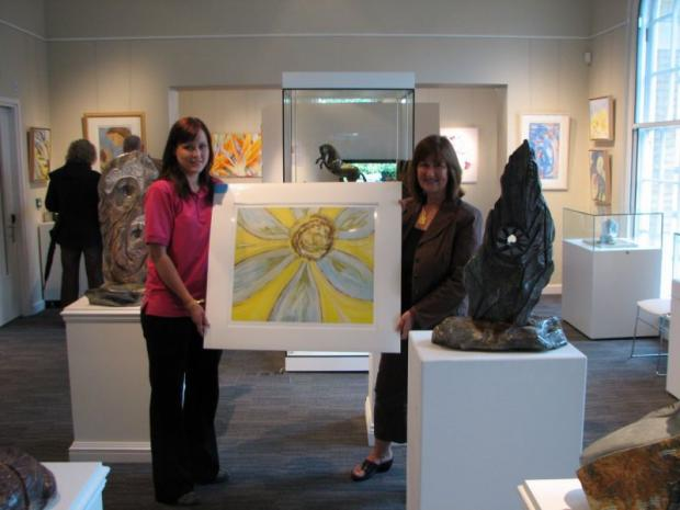Bridget Dumper (right) presents the limited edition print of Sunbloom to Michelle Coles of Naomi House