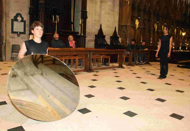 Emma Dixon holds the mirror, watched by Kimvi Nguyen, as part of The Companion of Space in Winchester Cathedral