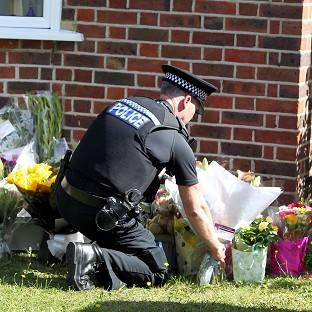 A police officer lays flowers outside the home of the victims