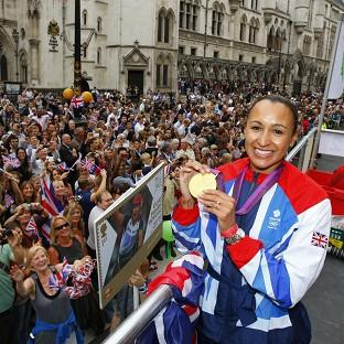 Heptathlete Jessica Ennis shows the crowd her gold medal as the parade passes the Royal Courts of Justice
