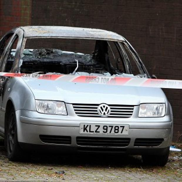 A burnt out car which people are linking to a fatal shooting in Newtownabbey, Co Antrim