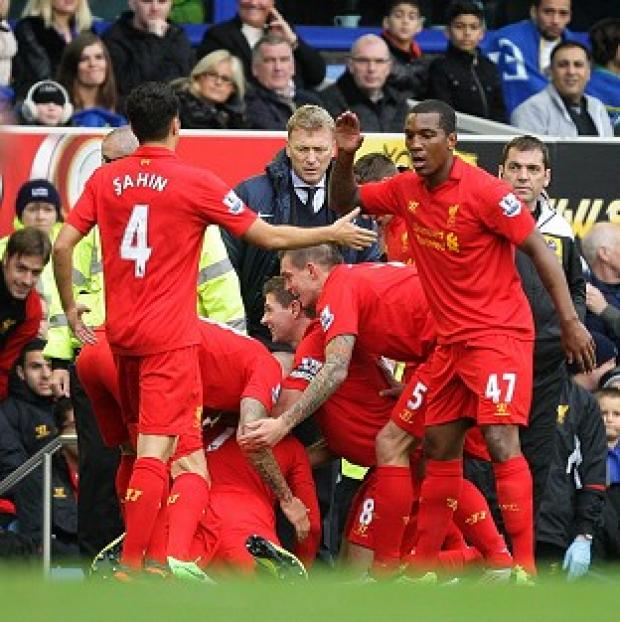 Luis Suarez, on floor, celebrates Liverpool's first goal by diving in front of Everton manager David Moyes
