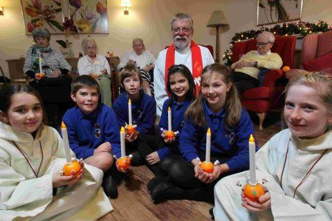 (l-r) St Peter's pupils Pippy Whiles, 10, John Bentley, 10, Oliver Radakin, 10, Petra Finlay, 10, Isabella Curtis, 10 and Muireann Conway, with Rev Mike Gardner (centre) and residents at St Catherines View Care Home