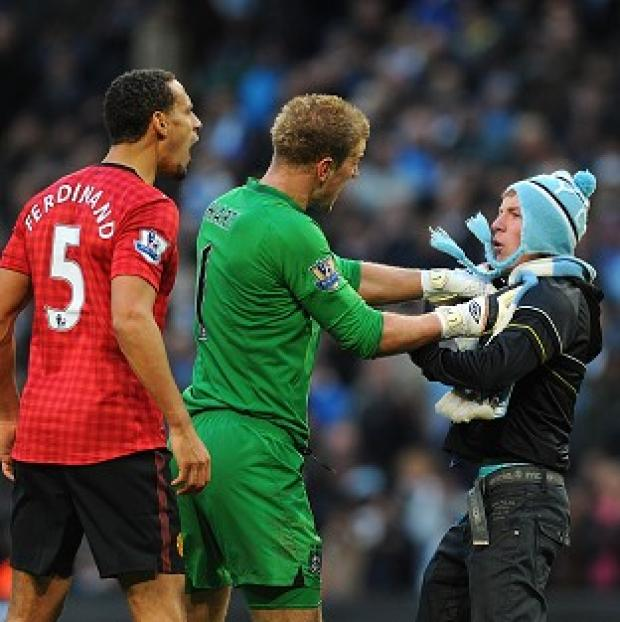 Rio Ferdinand, left, was hit by a coin thrown by Manchester City fans