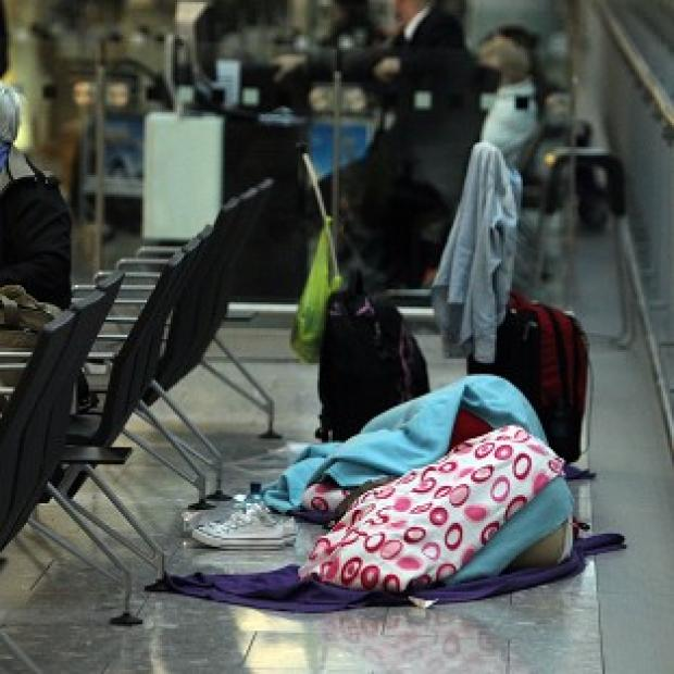 Passengers sleep after their plane was delayed at Heathrow Airport as ice and thick fog descended on the UK overnight