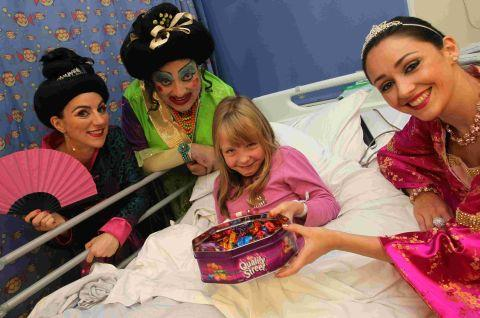 Ellie O'Donnell, eight, meets the stars of Aladdin (l-r) Kali Hughes (Empress of China), Julian Eardley (Widow Twankey) and Felicity McCormack (Princess Jasmine)