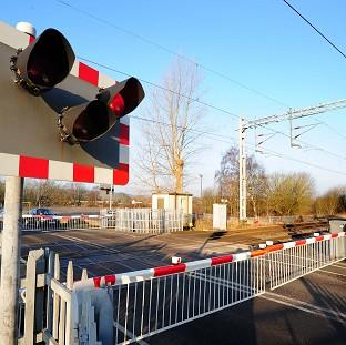 A man died after a car was hit by a freight train at a level crossing