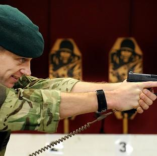 Royal Marine Sergeant Steve Lord tests a Glock 17 9mm pistol, on an indoor shooting range at Woolwich Barracks