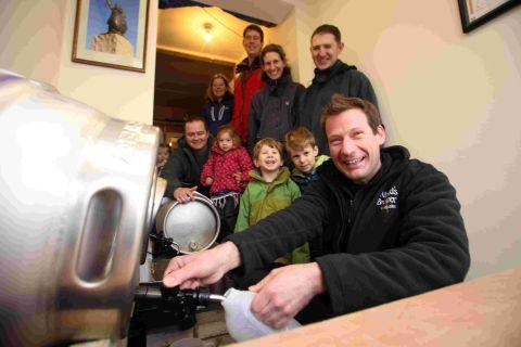 Eager punters (and their children) look on as founder Steve Haigh pours the first of the beer for direct sale.