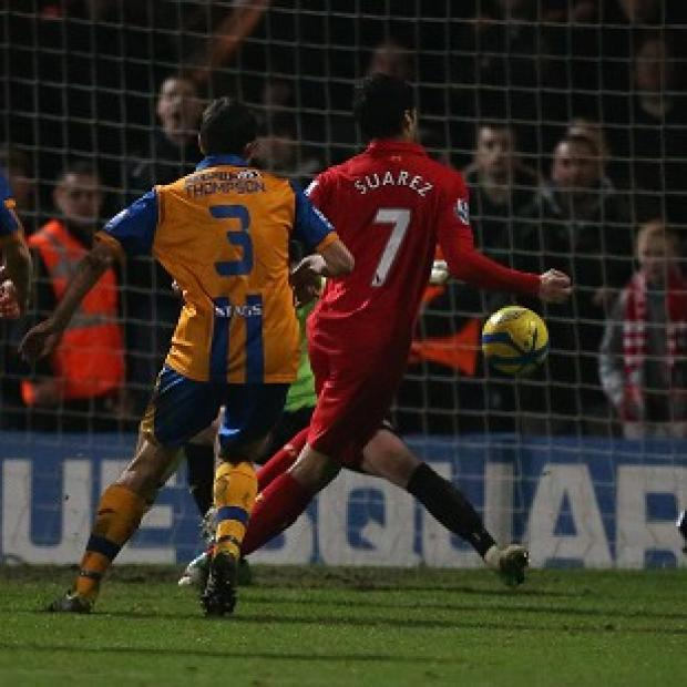 Luis Suarez, right, denies intentionally handling the ball in the Mansfield game