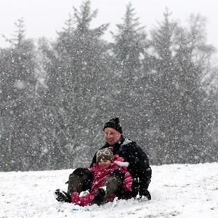 Davie Booth and three year-old daughter Freya enjoy sledging in Doune, central Scotland