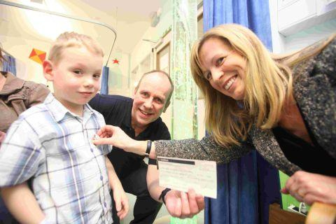 Tony Mant, who shaved his beard for the Magic Wand Appeal, presents the money to the Childrens Ward