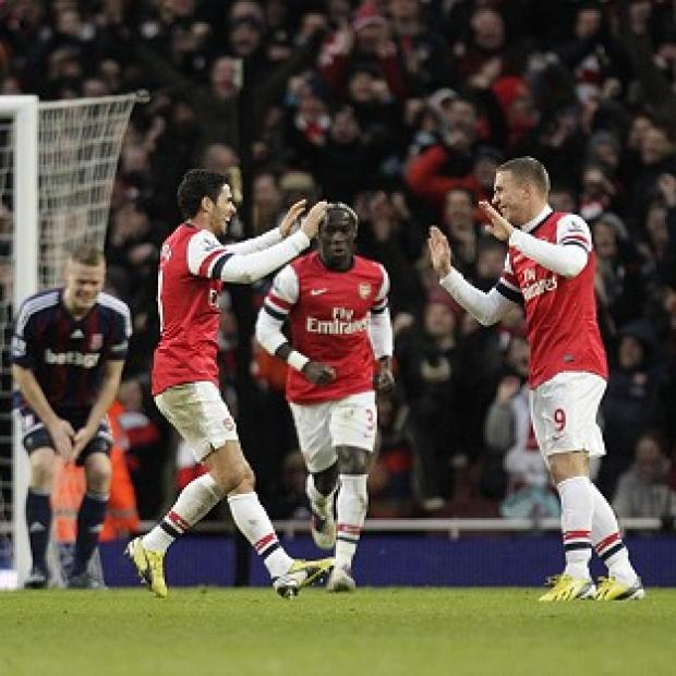 Lukas Podolski, right, netted from a free-kick as Arsenal beat Stoke