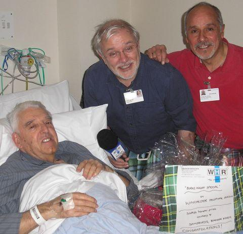 Patient David Farmer accepts his prize of Scottish goodies from volunteers Paul Blitz and Ron Venturi