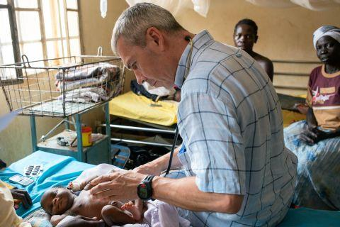 Dr Simon Struthers, project leader, treats a child in South Sudan. Photograph by Tom Price.