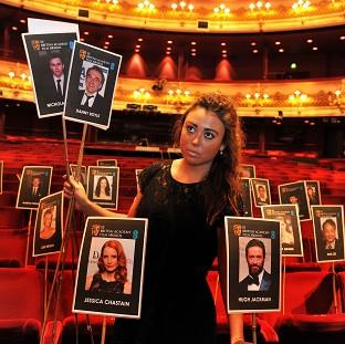 Rosie Wiseman places photos of actors and actresses on seats at the Royal Opera House in Covent Garden