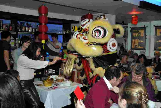Pamela Cheng of the Mayflower Chinese Restaurant giving Lai See to a Chinese lion