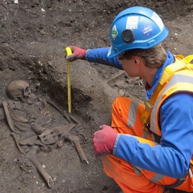 Carefully laid out skeletons thought to be from a 14th century burial ground have been discovered in London (Crossrail/PA)