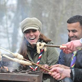 The Duchess of Cambridge cooks around a campfire during her visit to a Scout activity centre