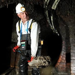 Thames Water Catchment Engineer Rob Smith works to clear a blockage of fat from part of London's sewer network