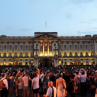 Crowds gather outside Buckingham Palace after an easel was placed in the forecourt to announce the birth of a baby boy