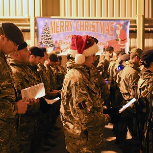 Soldiers gather at Camp Bastion field hospital, Afghanistan, for a carol service led the UK Joint Force Medical Choir, with music by the Royal Artillery band.