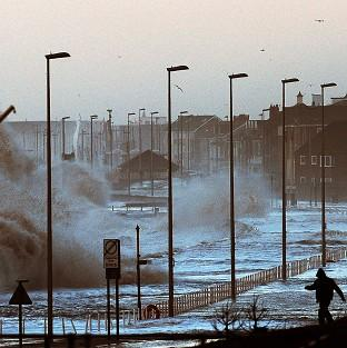 Hampshire Chronicle: Water covers the coastal roads at Clevelys near Blackpool as large waves crash over the sea defences as high tides and huge waves hit the west coast of the UK.