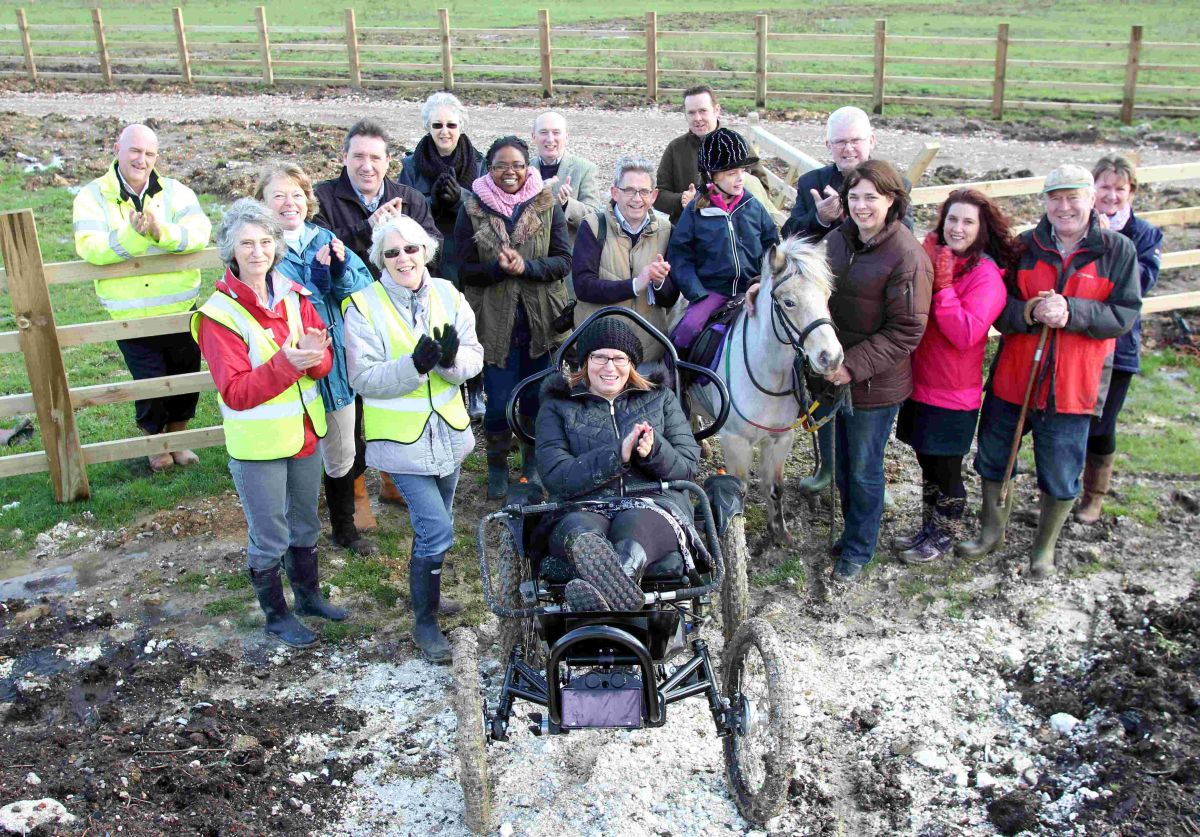 Emma Weavil in a BOMA electric powered off-road wheelchair with staff and guests on the remodelled chalk mounds celebrating the start of the project