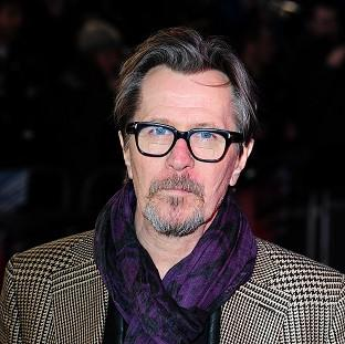 Gary Oldman arrives at the premiere of RoboCop