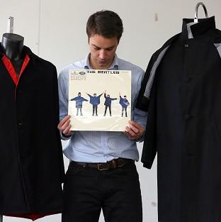 Auctioneer Paul Fairweather with jackets worn by George Harrison and Ringo Starr