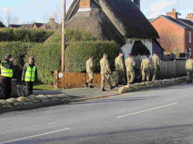 Troops arrive to help the villagers. To the left can be seen parish clerk, Sue Hedges, whose efforts have been praised by residents.