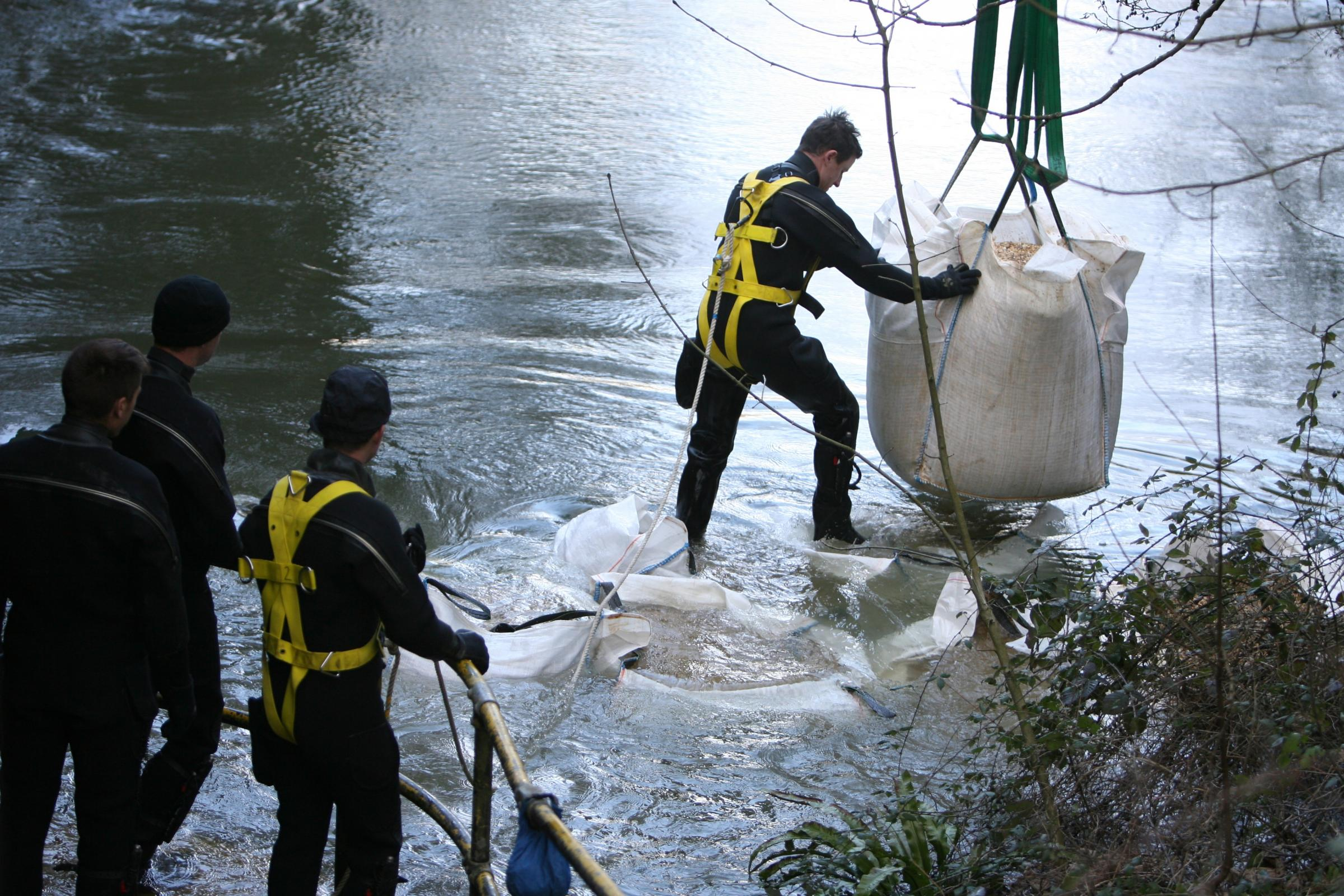 Army engineers lower huge bags of gravel into the River Itchen at Kings Worthy in an attempt to slow the flow of water downstream