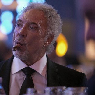 Sir Tom Jones smokes a cigar during a gala dinner