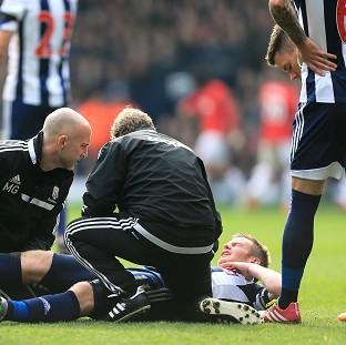 Hampshire Chronicle: Chris Brunt receives treatment during West Brom's match against Manchester United on Saturday