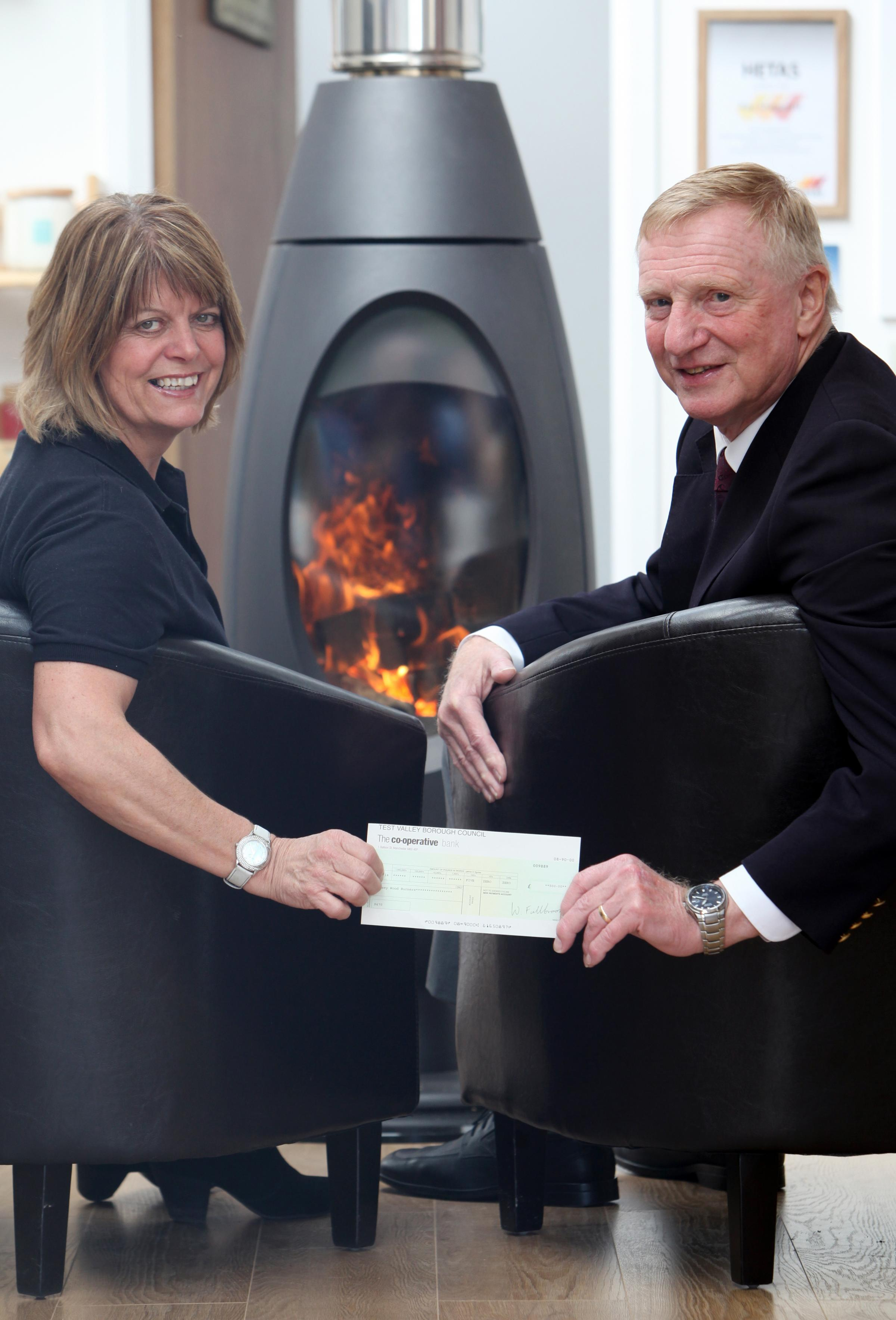 Test Valley councillor Tony Ward presents Angela Coleman with a cheque for £500 for her new woodburner business