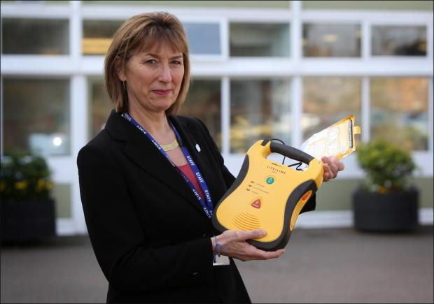 Mountbatten School's welfare officer Janet Barratt with a defibrillator