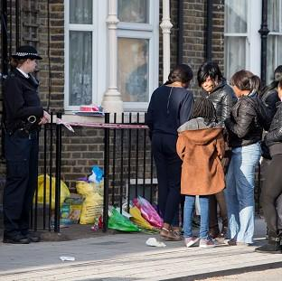 Hampshire Chronicle: A police officer watches as a group of people gather at the scene in Hackney where Shereka Fab-Ann Marsh, 15, died after a shooting