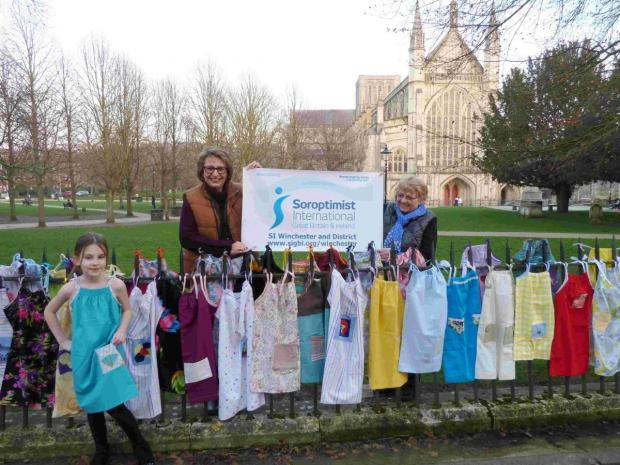 Seven year old Caitlin Scott modelling one of the pillowcase dresses, SI Winchester members Carol Forse and Gina Bird.