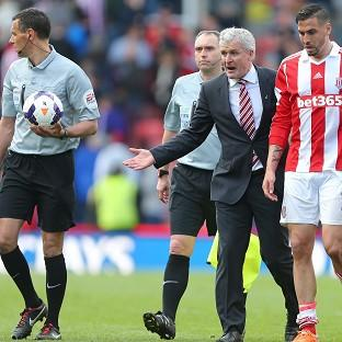 Mark Hughes, centre, was highly critical of the decisions made by referee Andre Marriner, left