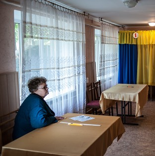 A polling station official rests after preparing booths at a polling station ahead of the regional referendum in the eastern Ukraine city of Luhansk (AP)