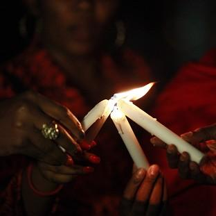 Hampshire Chronicle: People light candles during a vigil in Abuja to mark one month after the Nigerian schoolgirls were kidnapped (AP)