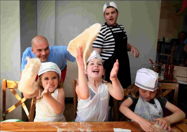 Hampshire Chronicle: Staff members Fabio Kersevan and Matt Bristown helped the children learn the best techniques for tossing the dough