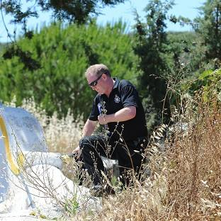 A British police officer scrambles over a wall as British and Portuguese officers investigate the disappearance of Madeleine McCann from Praia da Luz