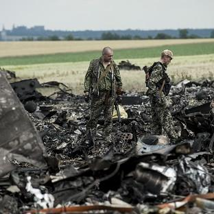 Hampshire Chronicle: Pro-Russian fighters walk past remnants of a downed Ukrainian army aircraft at the airport near Luhansk (AP)