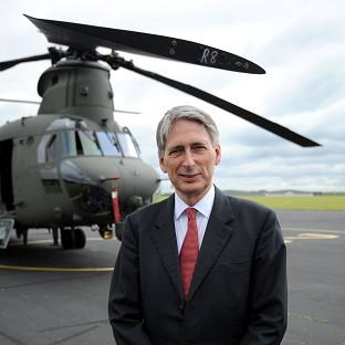 Hampshire Chronicle: Defence secretary Philip Hammond stands in front of the new Chinook Mk6 helicopter during its unveiling at RAF Odiham in Hampshire